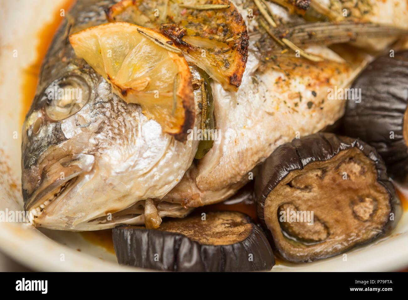 Baked dorado fish with lemon and eggplant. Stock Photo