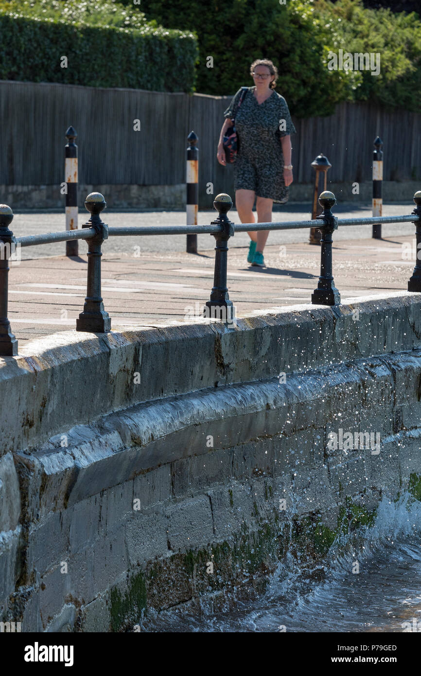 woman walking along a sea wall or seafront with waves splashing on the sea wall. - Stock Image