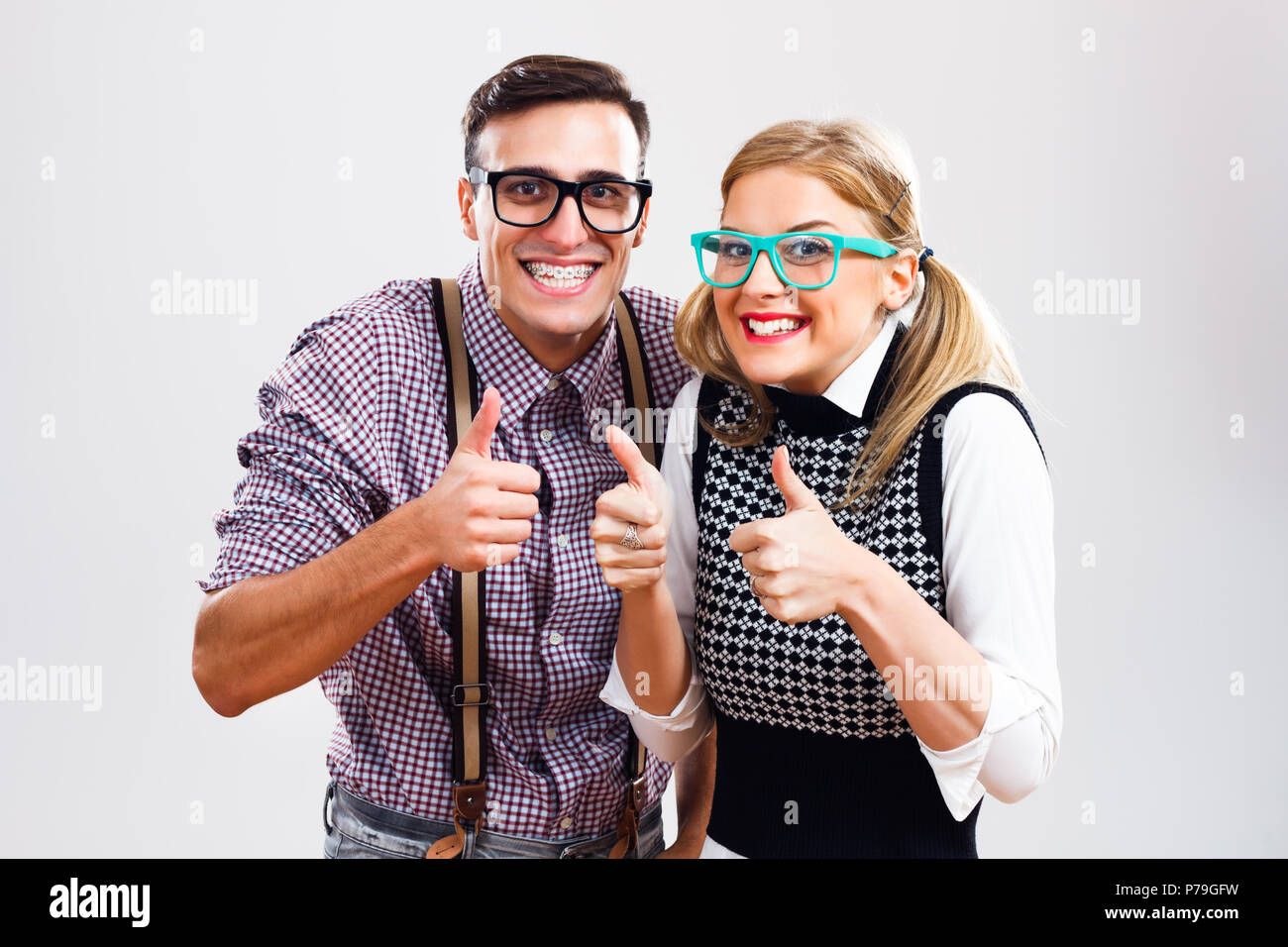 Happy nerdy couple showing thumbs up - Stock Image