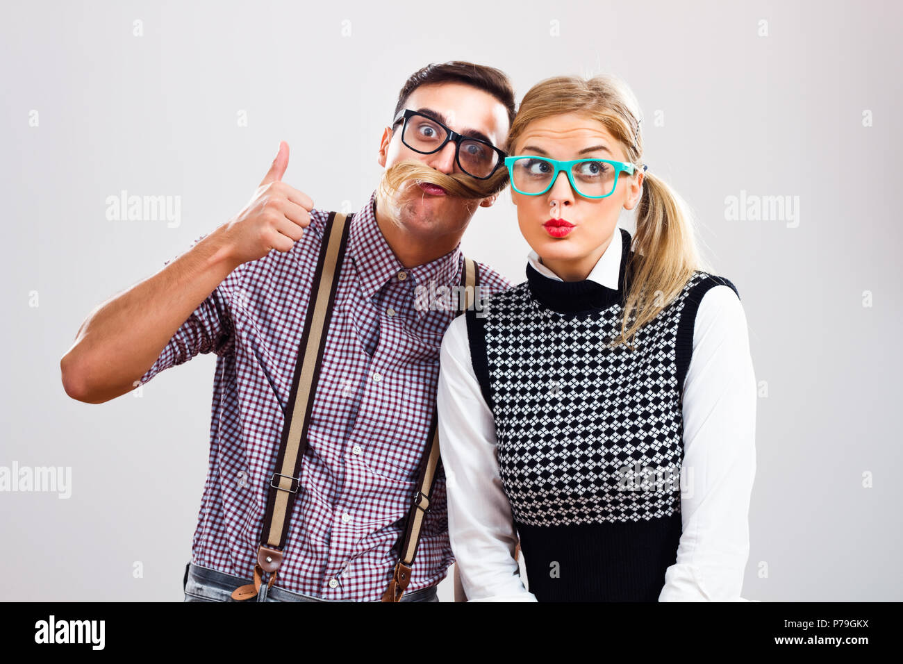 Portrait of two cute nerds having fun. - Stock Image