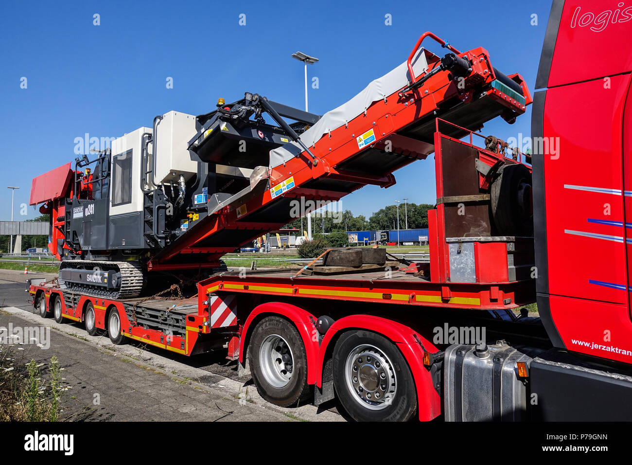 AACHEN, NRW, GERMANY - JUNE 30, 2018: Heavy hauling of a mobile jaw crusher, transported on a special low-loader trailer truck. - Stock Image