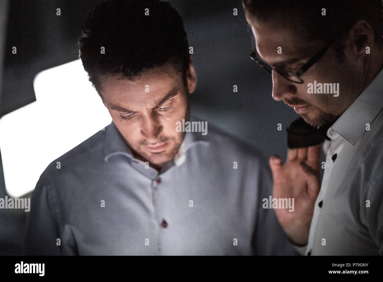 close up.two business men in the workplace in the evening - Stock Image