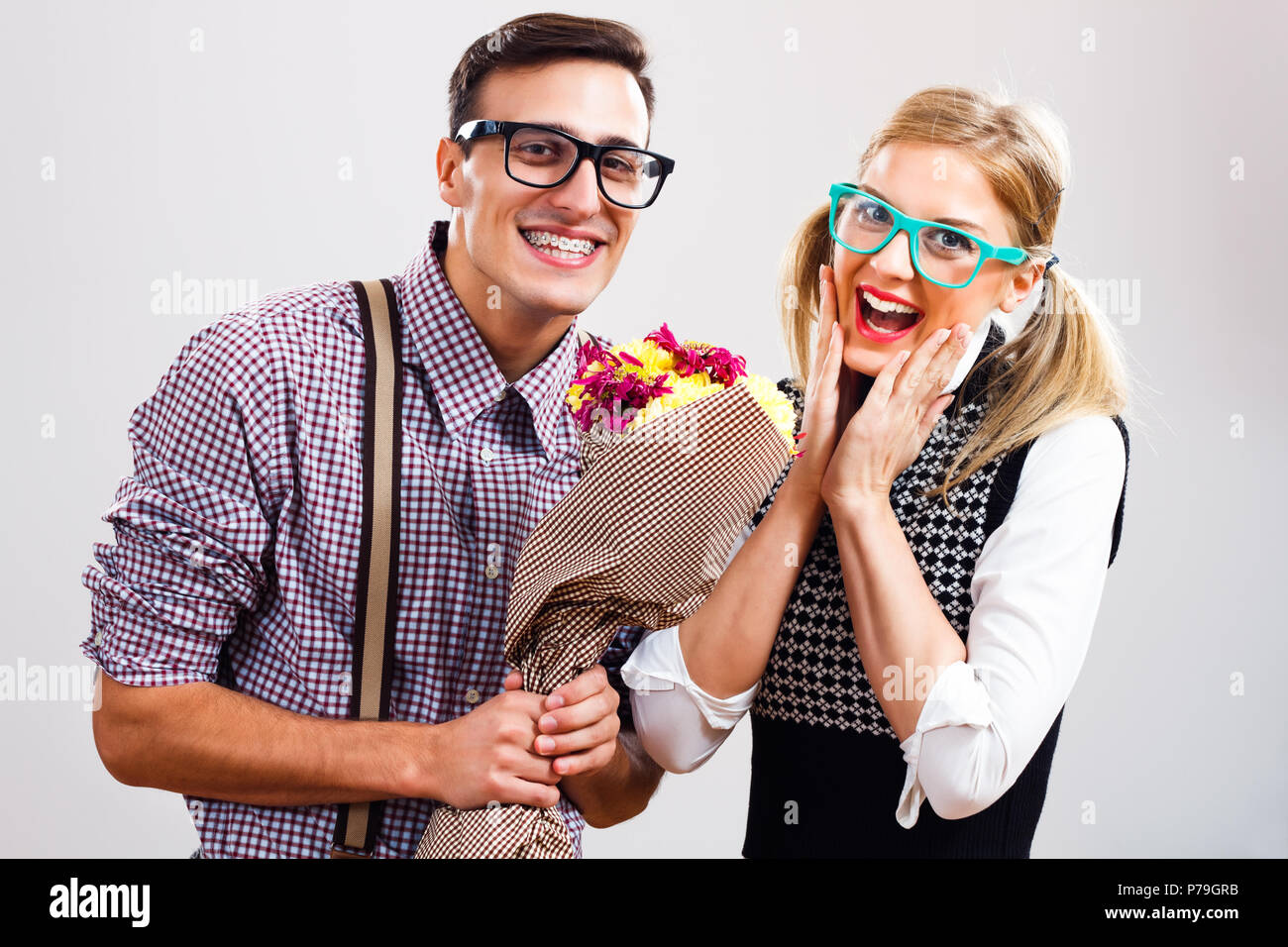 Nerdy man is giving flowers to his nerdy lady. - Stock Image