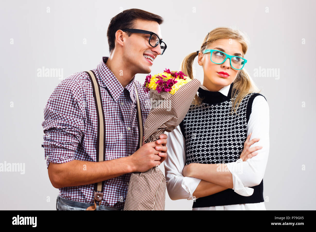 Nerdy man wants  that her nerdy girlfriend forgive him because of something. - Stock Image