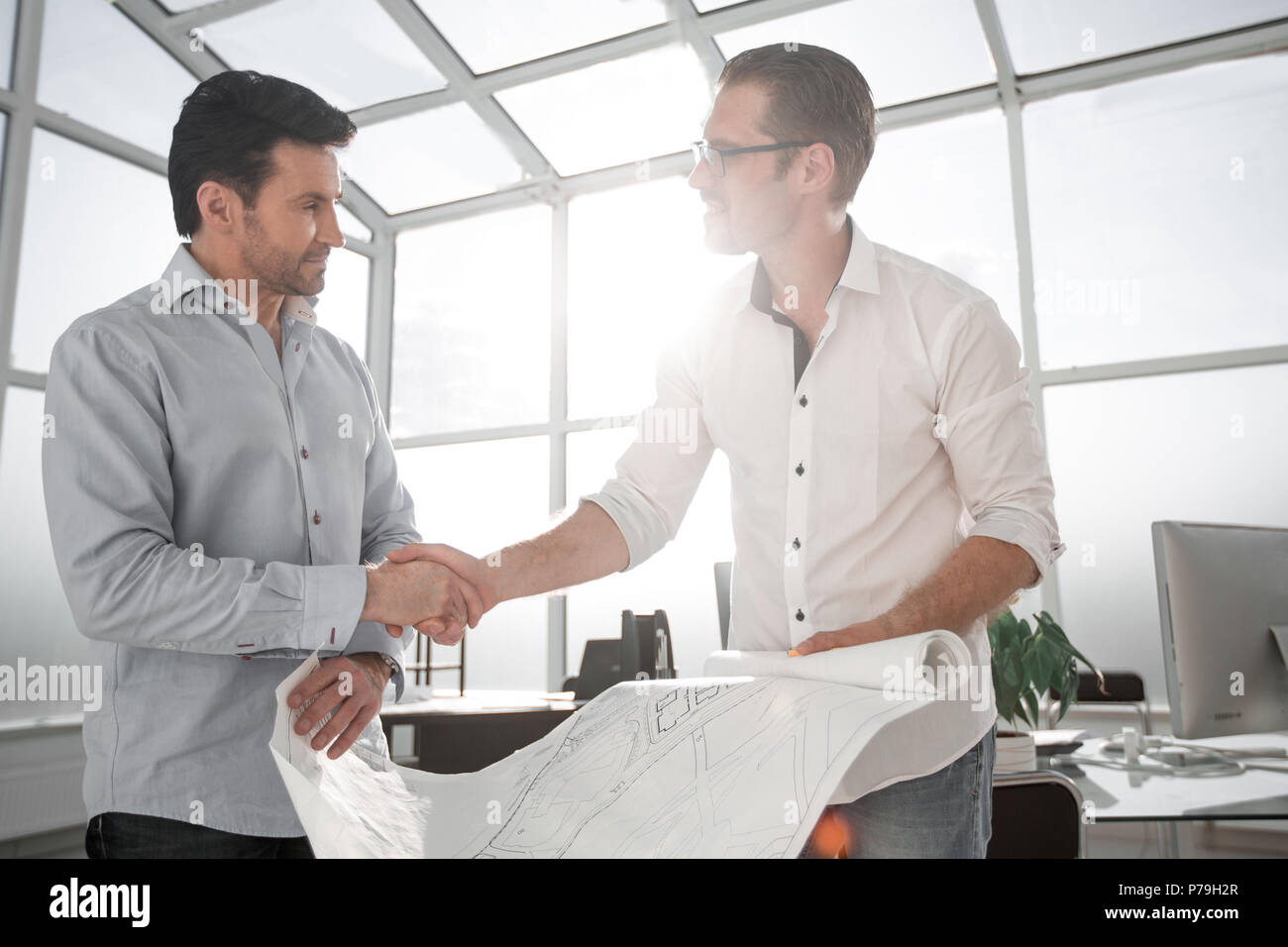 architect and client handshake in the office - Stock Image