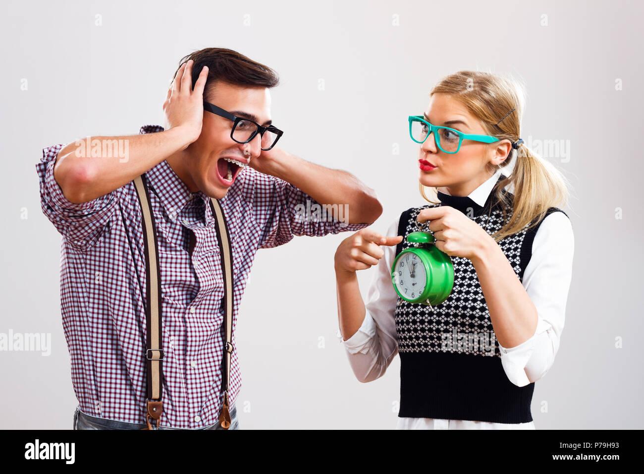 Nerdy woman showing clock to her nerdy boyfriend. - Stock Image