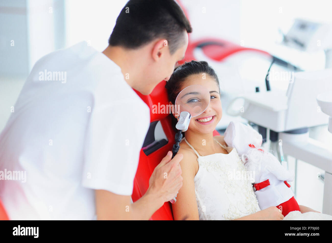 Beautiful smile with white teeth. A dentist examines the oral cavity of a young beautiful girl through a magnifying glass in the dental office. - Stock Image
