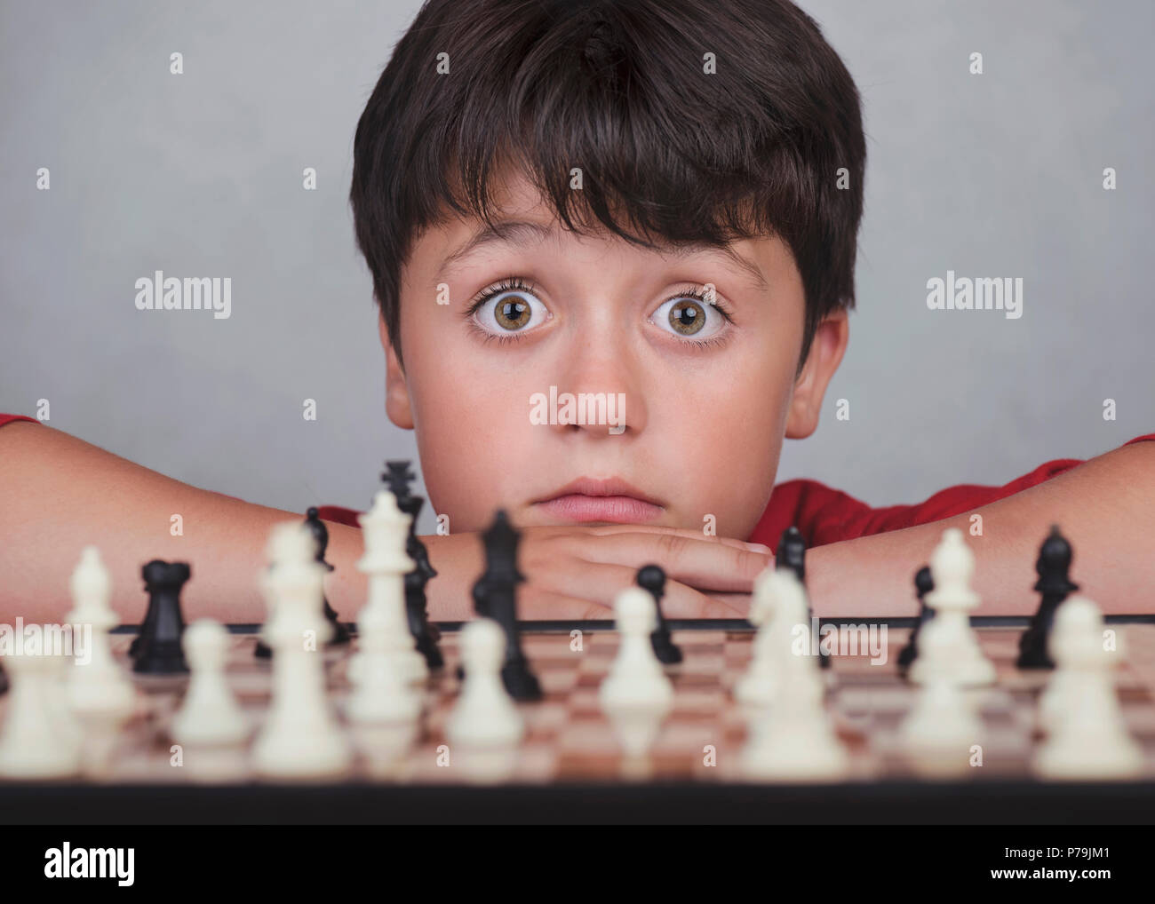 Little boy playing chess on gray background - Stock Image