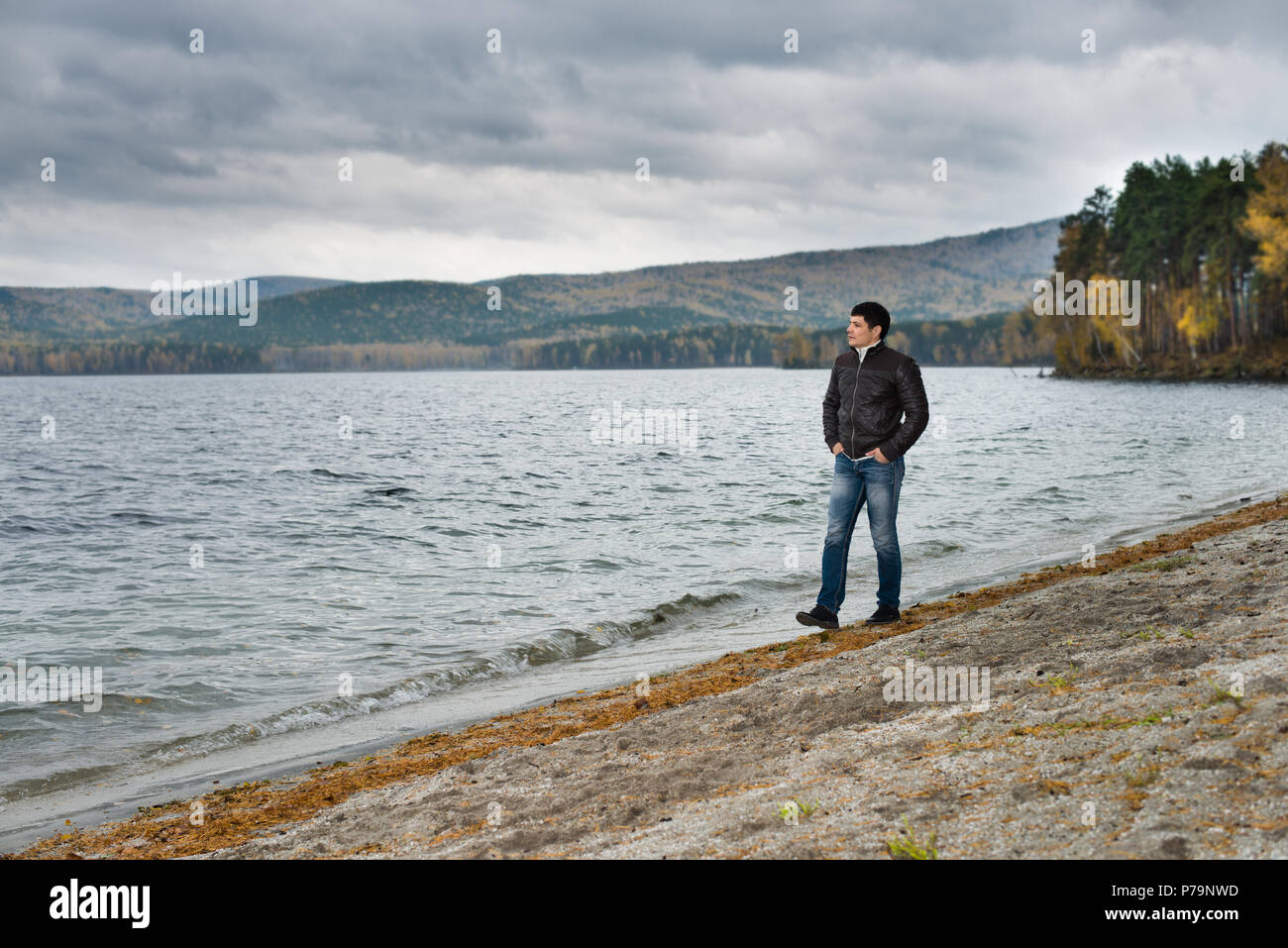 young guy outdoor on water moorage for boat, in autumn cold overcast day - Stock Image