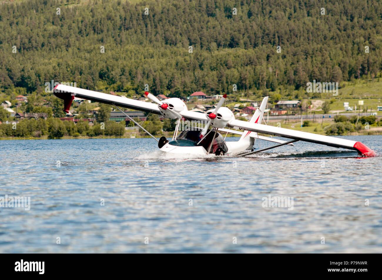 white twin-engine  light   hydroplane make landing or takeoff on water - Stock Image