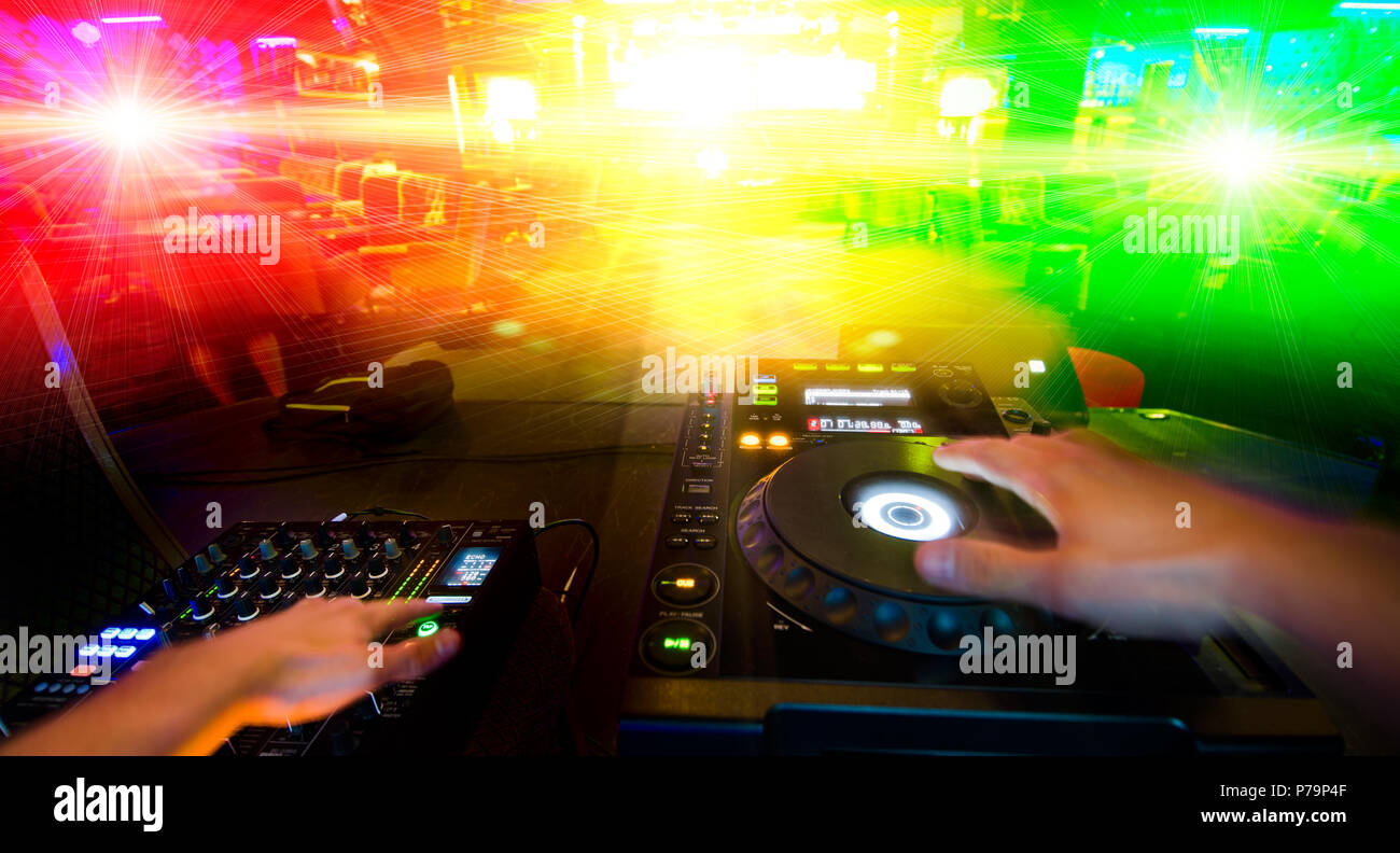 disc jockey with sound control desk - Stock Image