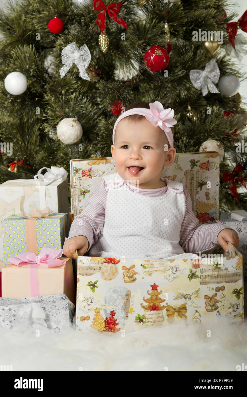 one-year-old little girl solemnize Christmas, sit under Christmas ...