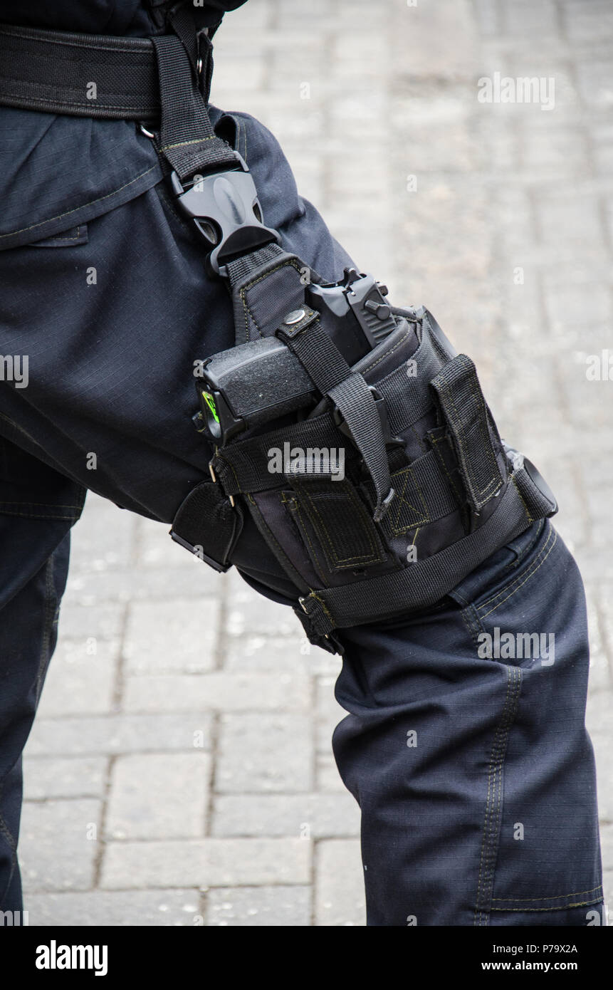 Leg of a policeman in which a firearm is found, concept of security Stock Photo