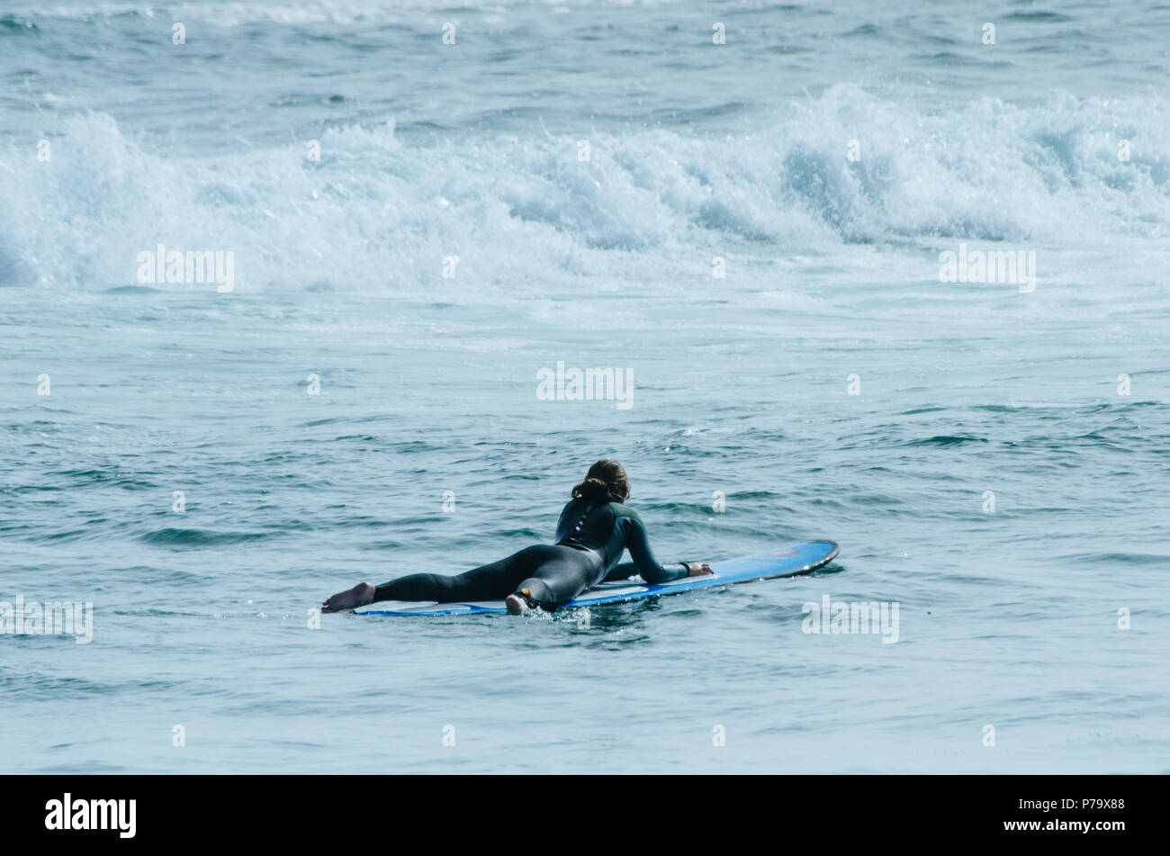A beautiful girl at the beach with her bodyboard - Stock Image