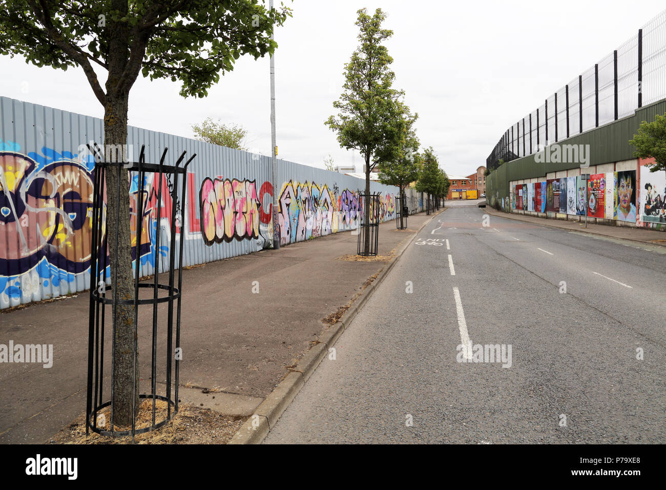 Political grafitti covers the Peace Wall in Belfast, Northern Ireland. The walls were erected to seperate the Republican and Loyalist populations duri - Stock Image
