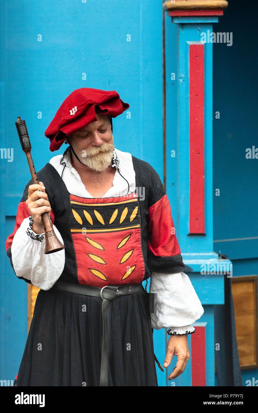 International Minstrel Troupe Rauschpfeife performer from the group Wolgemut. Wearing bright red and black Tudor period costume at the MD Ren Fest. - Stock Image
