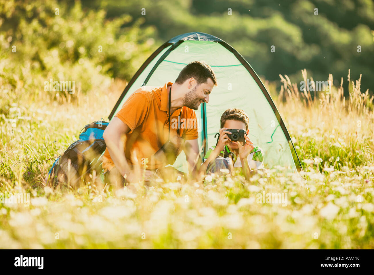 Father and son are camping in nature. Little boy is photographing. - Stock Image
