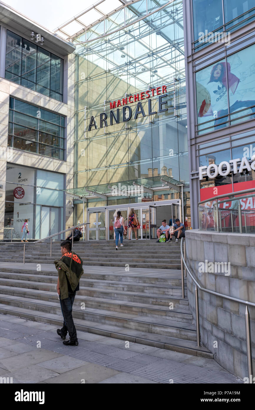 A young man walks past the entrance to the Manchester Arndale Centre. Manchester, UK - Stock Image