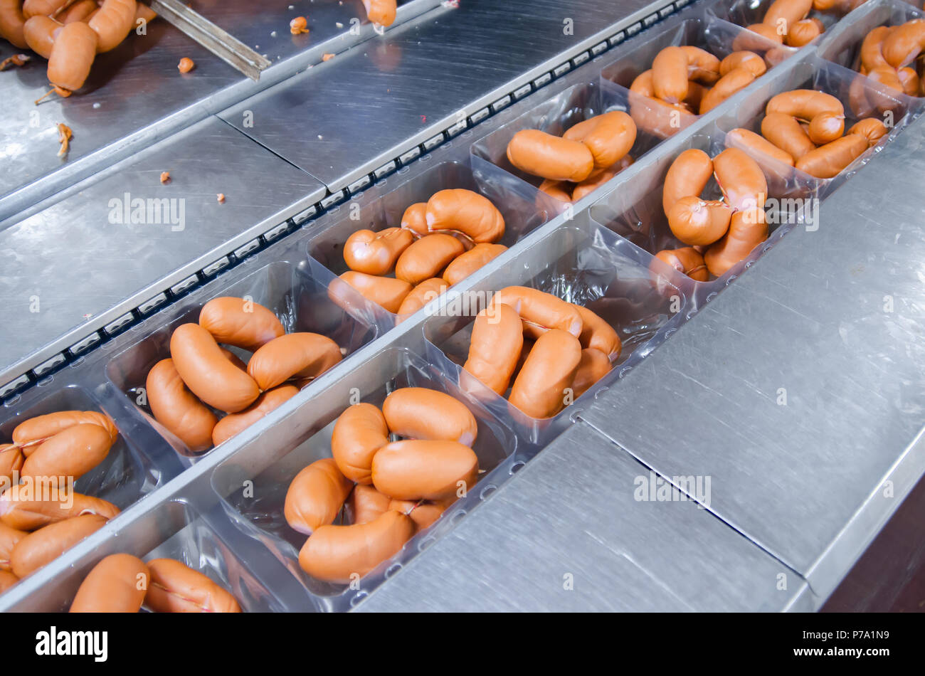 Sausages. Packing line of sausage. Industrial manufacture of sausage products - Stock Image