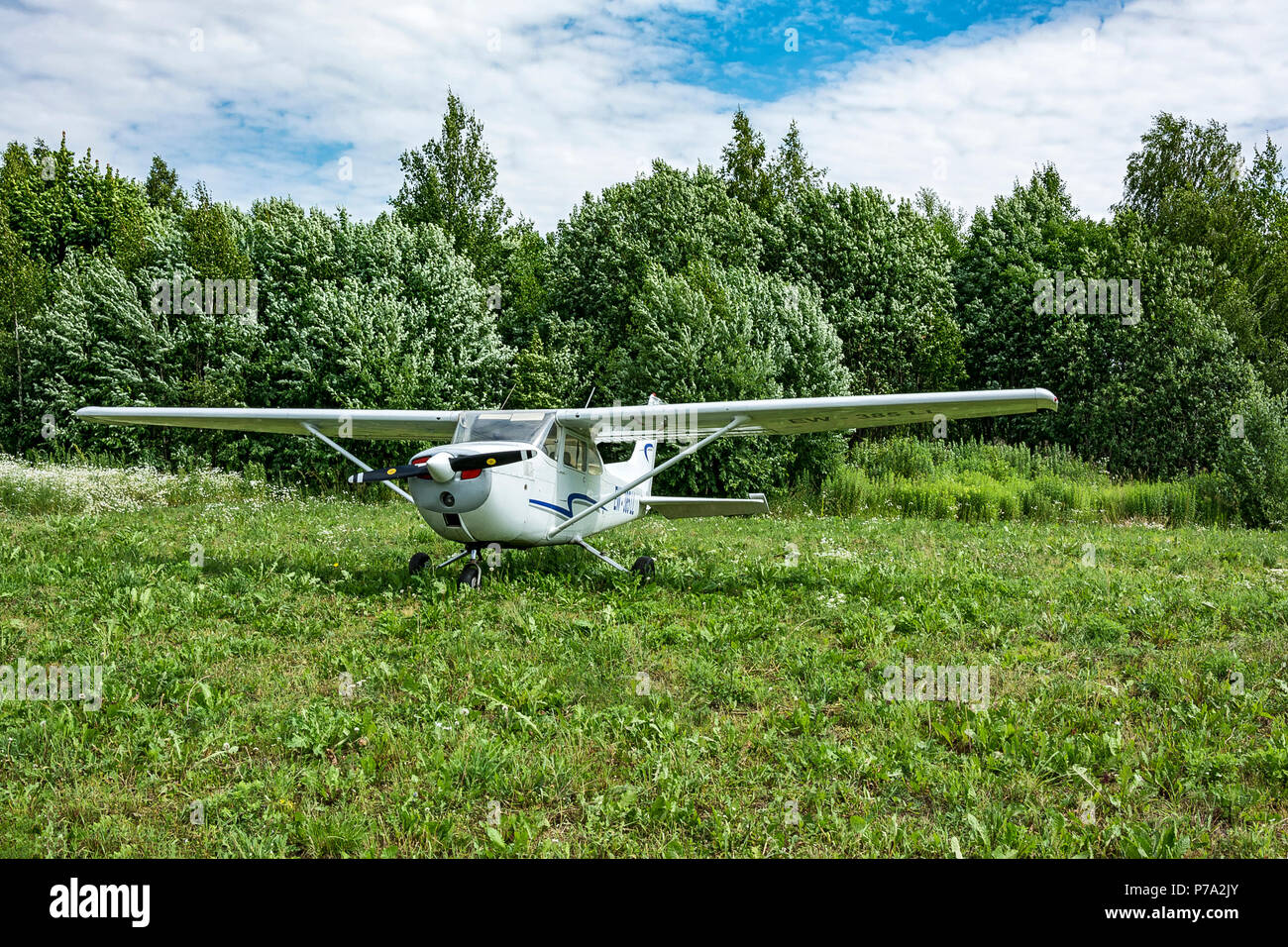 Minsk, Belarus - June 21, 2018: Single-engine aircraft stands on the green grass near the forest. - Stock Image