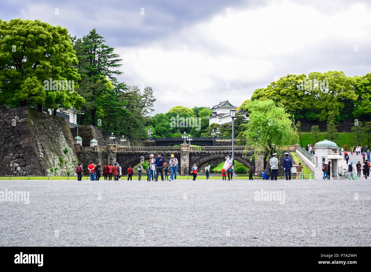 Tourists visiting Seimon Ishibashi Nijubashi Bridge, the Tokyo's most famous bridge at the Imperial Palace in Tokyo, Japan - Stock Image