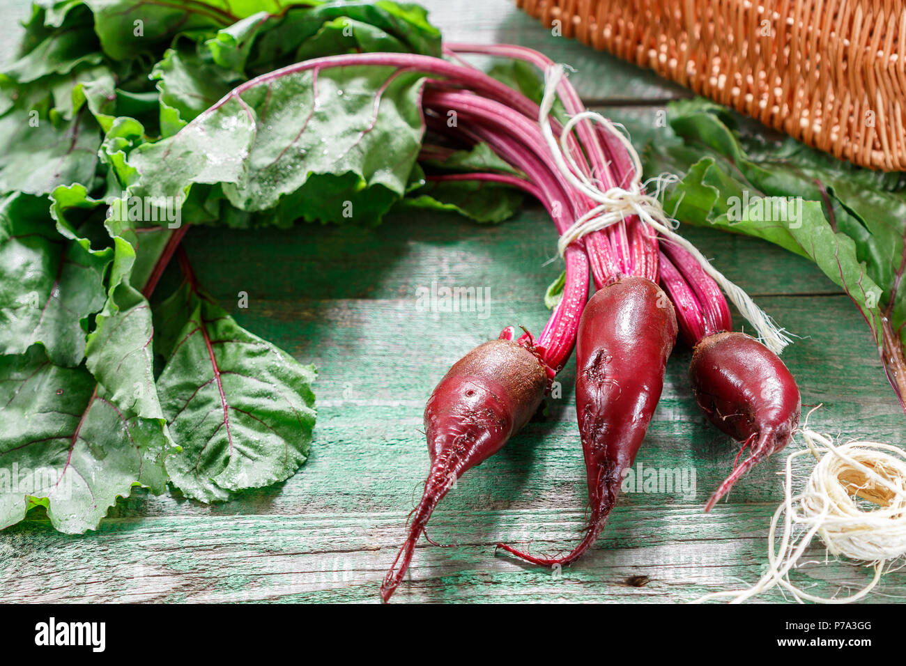 Organic red beets (beetroot) with green leaves on an old wooden table. Rustic style. Selective focus, copy space Stock Photo