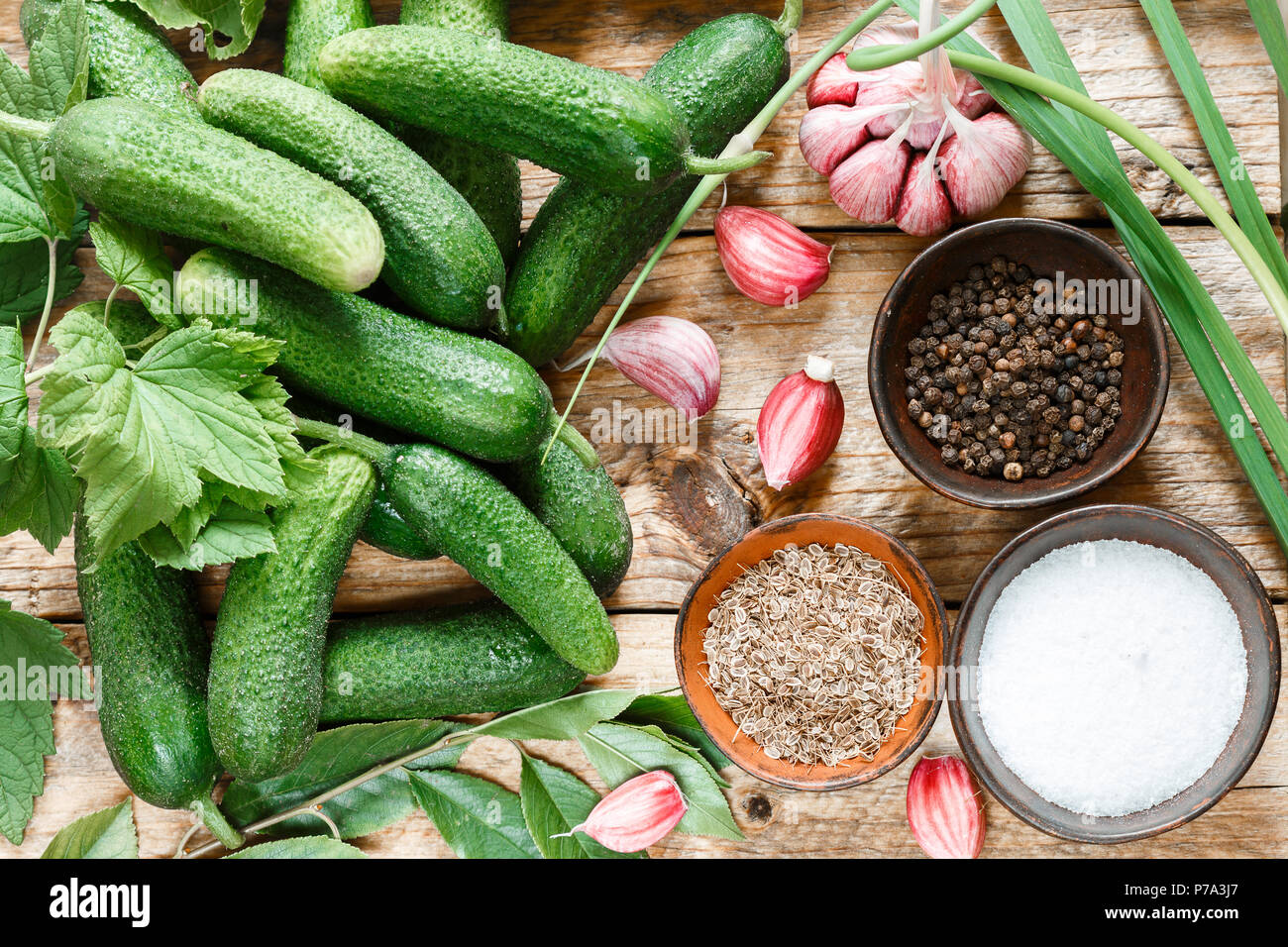 Ingredients for preservation on an old wooden table-cucumbers, garlic, dill seed, pepper, salt, seasonings and spices . Selective focus - Stock Image