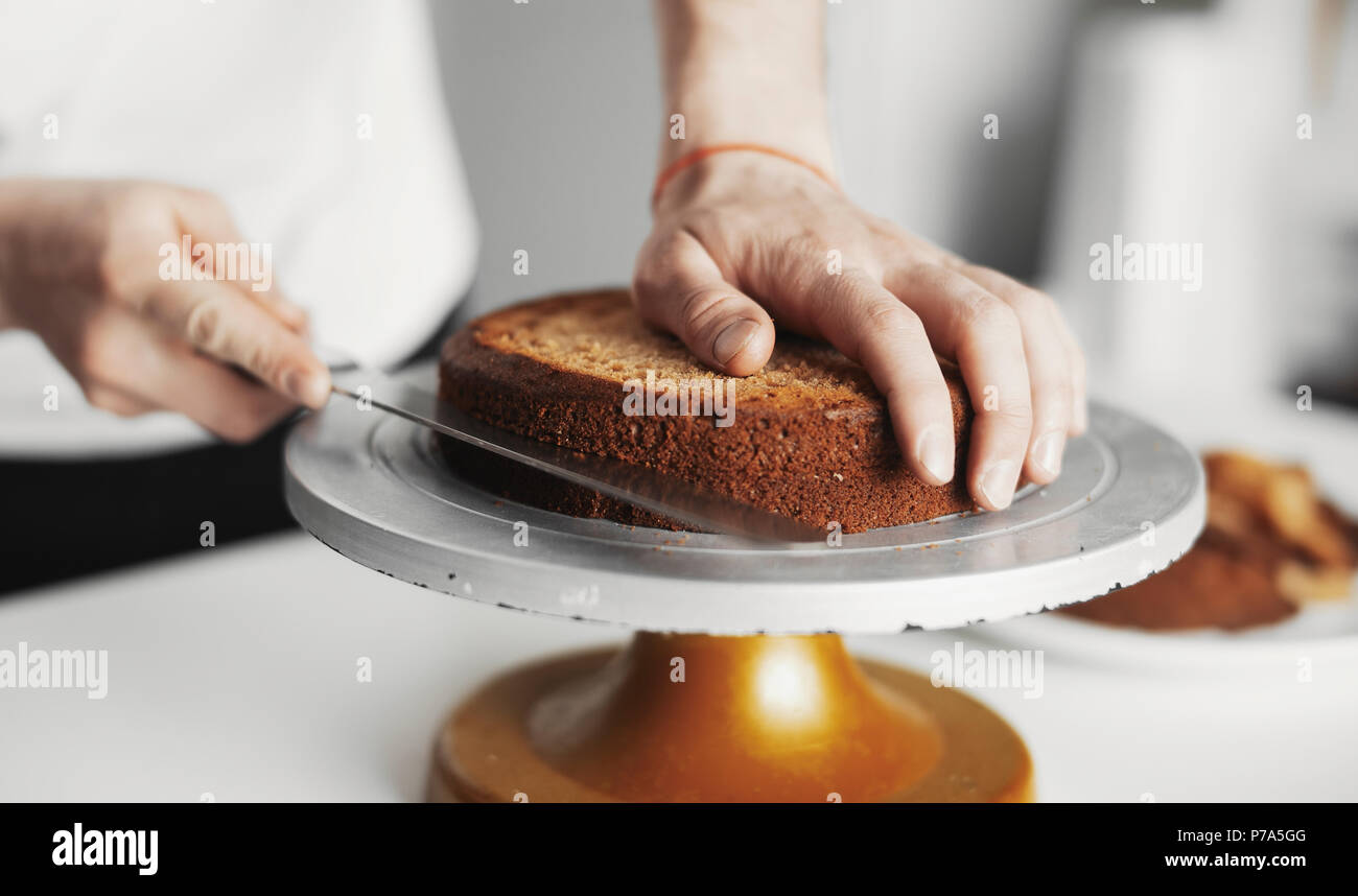 Close up of cook cutting cake on a cake stand. - Stock Image
