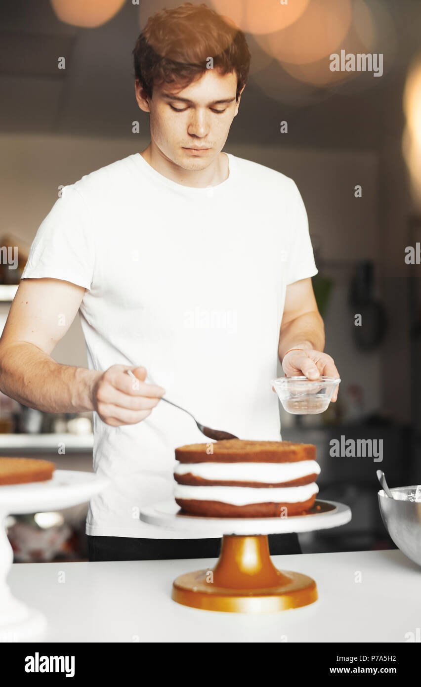 Young attractive man smearing sugar syrup on chocolate cake. - Stock Image