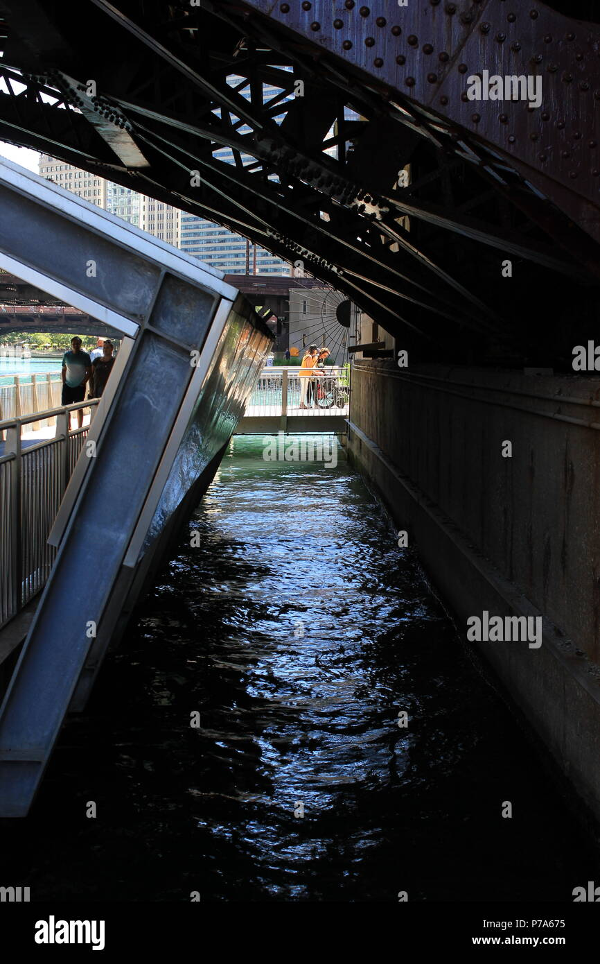 Under the Clark Street bridge along the Chicago River at downtown Chicago's River Walk in Illinois. - Stock Image