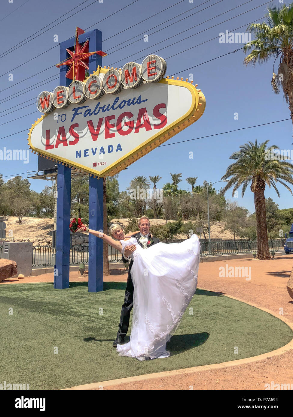 Bride and groom at Welcome to Fabulous Las Vegas sign. Newlywed couple pose for photo, the bridegroom lifting up the bride with bouquet in his arms - Stock Image