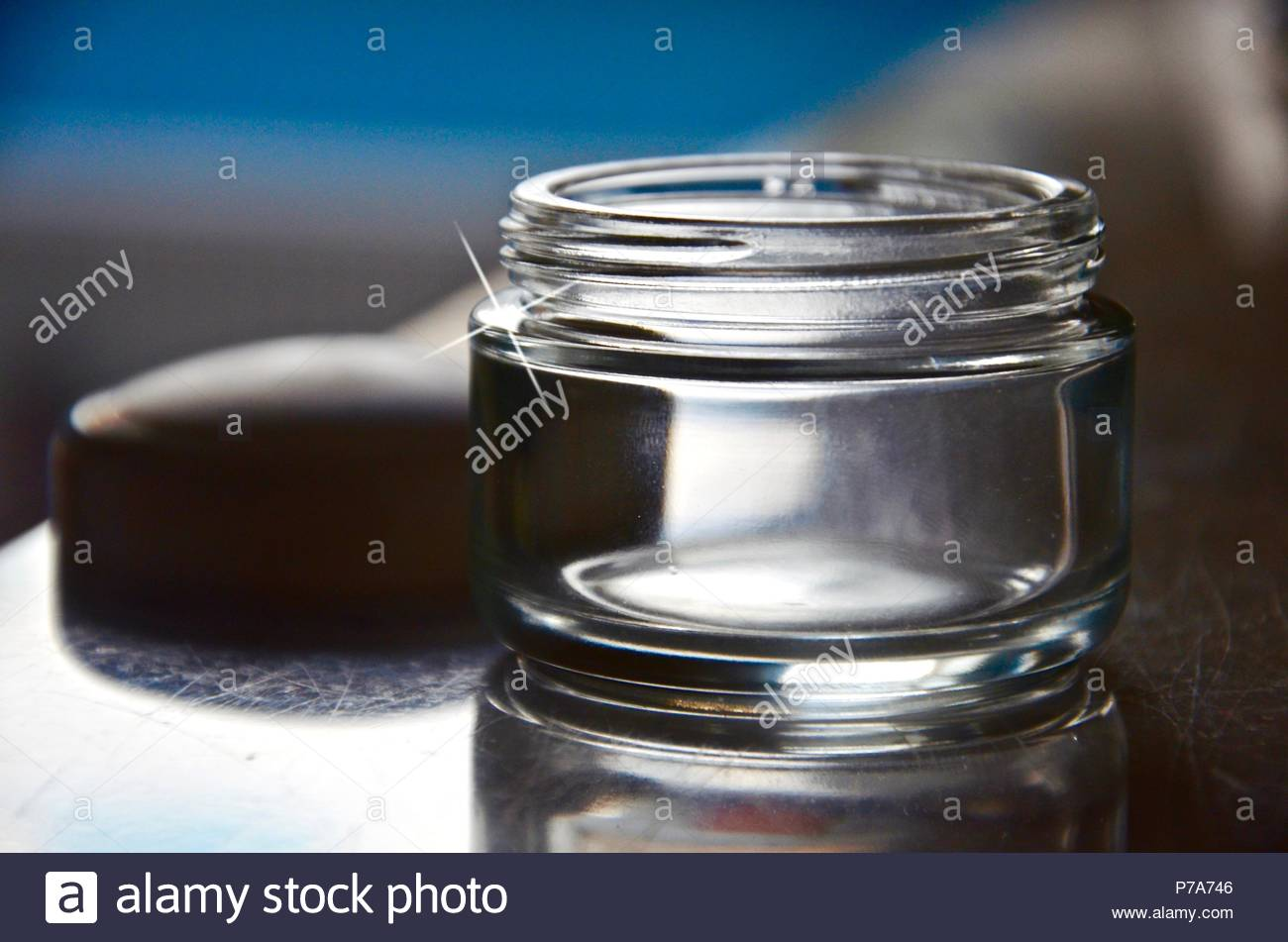 Empty face cream pot of glass with cover, blurred background, cosmetics, bright, industry, environment, blue, shiny, cosmetics industry, advertising - Stock Image