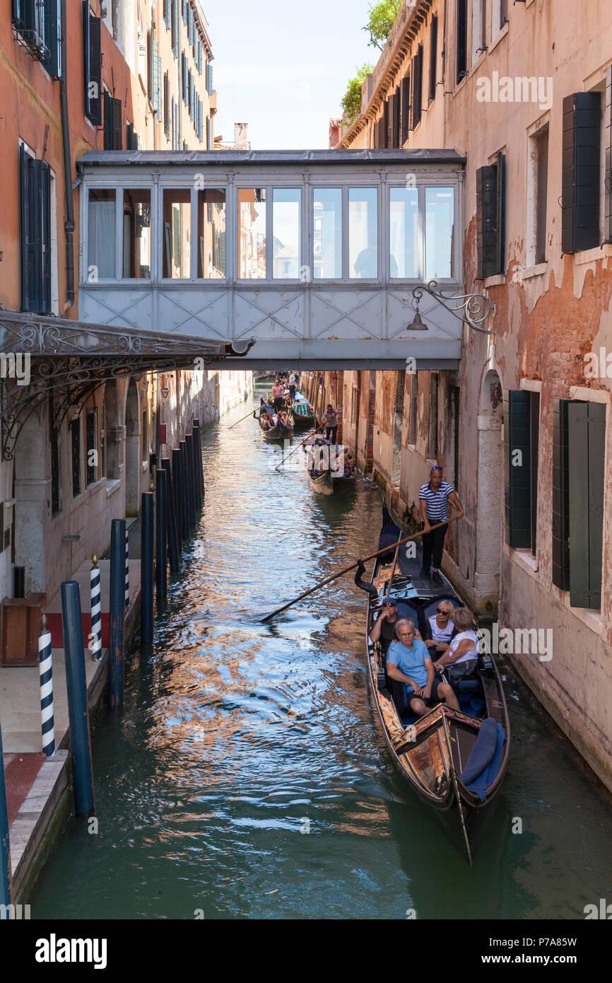Gondolas with tourists in Rio del Vin, Castello, Venice, Veneto, Italy passing under the covered pedestrian bridge between buildings of the Danieli H - Stock Image