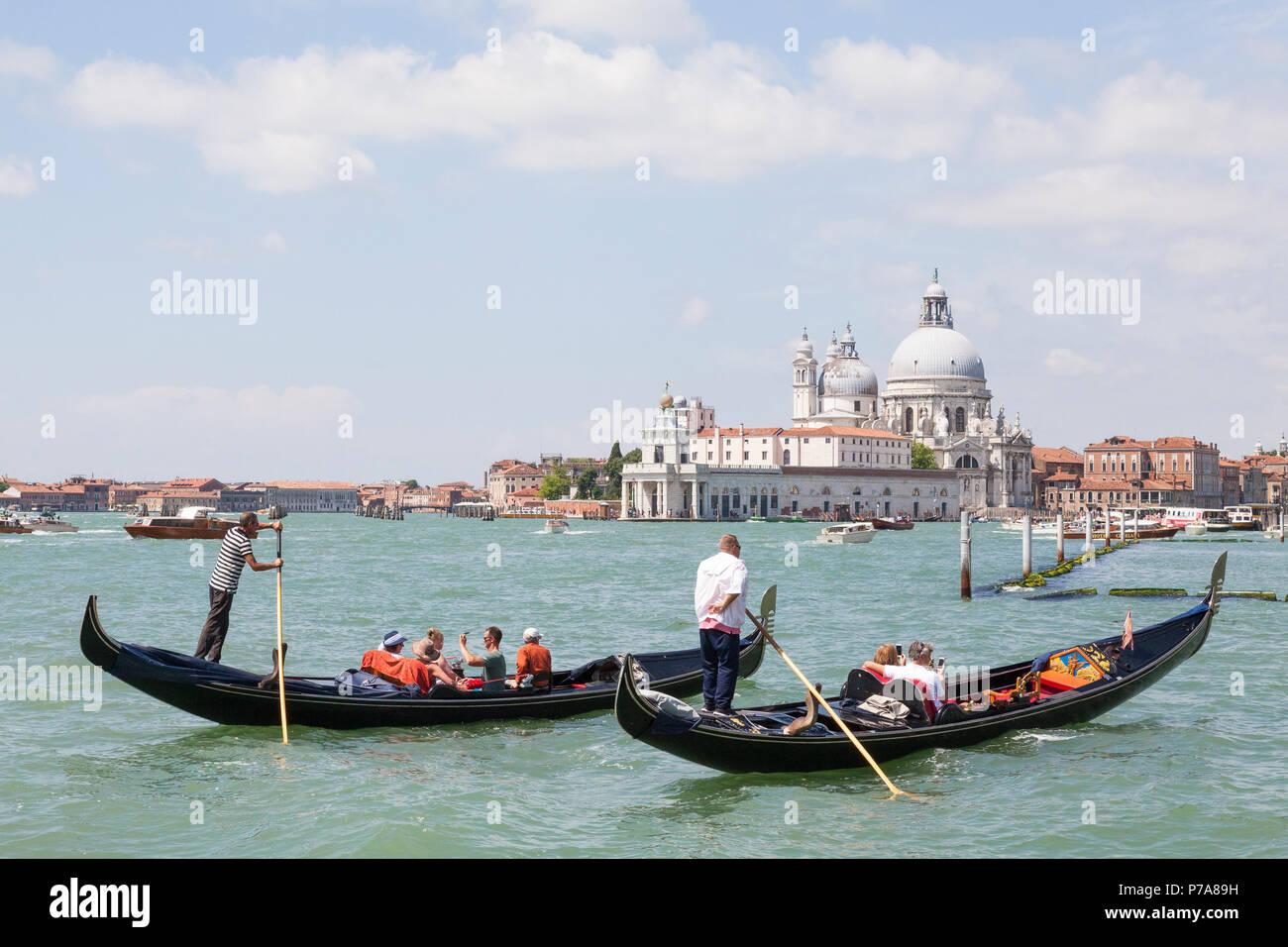 Two gondoliers rowing tourists in gondolas St Marks Basin, Venice, Veneto, Italy with Punta della Dogana and Basilica di Santa Maria della Salute - Stock Image