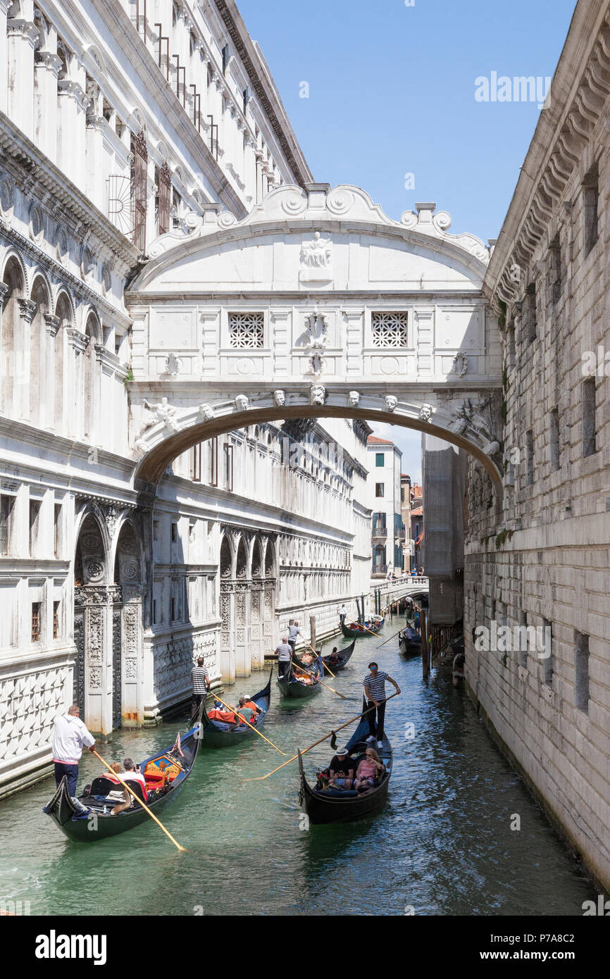 Gondolas with tourists rowing under the Bridge of Sighs (Ponte dei Sospiri) , San Marco, Venice, Veneto,  Italy between the Doges Palace and Venetian  - Stock Image