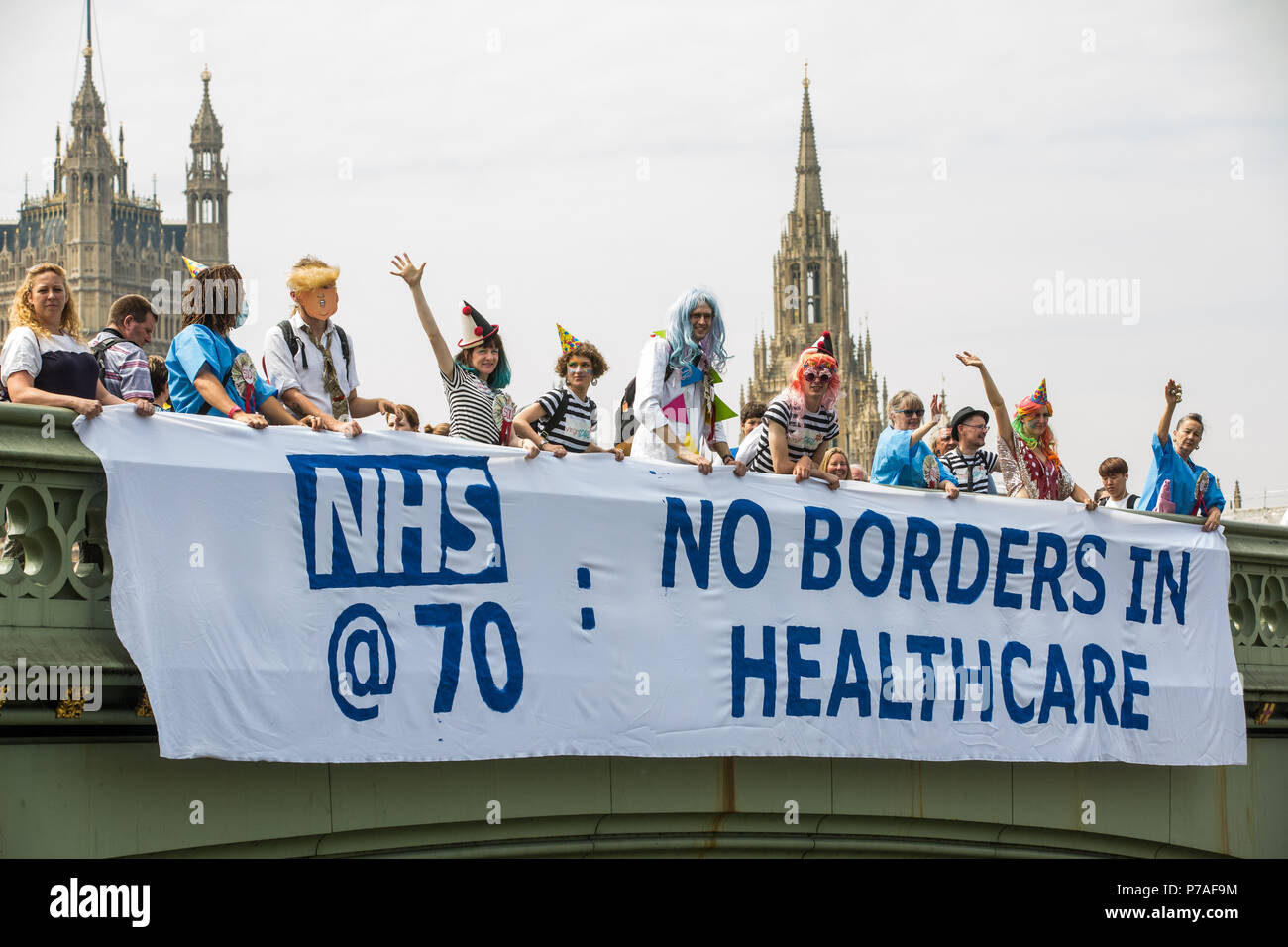 London, UK. 5th July, 2018. Activists from Docs Not Cops and the NHS Anti-Swindle Team drop a banner from Westminster Bridge reading 'NHS@70: No Borders in Healthcare' on the 70th birthday of the National Health Service. Docs Not Cops is a group comprising doctors, nurses, HIV activists, students, teachers and laypeople who believe that health care is a human right and are opposed to government policies which might make anyone fear visiting a doctor for reasons of cost or immigration status. Credit: Mark Kerrison/Alamy Live News - Stock Image