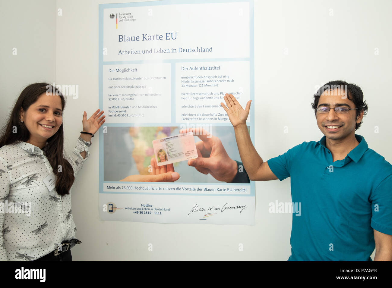 05 July 2018, Nuernberg, Germany: Hymalai Bello, electrical engineer from Venezuela, and Vasant Karasulli, software developer from India infront of an Infograph on the 'Blue card' for foreign skilled workers in the Federal Office for Migration and Refugees (Bamf). Nearly 77,000 highly qualified immigrants from non-EU countries have so far been able to work with a so-called Blue Card in Germany. Much of it in highly sought-after occupations - such as an engineer, natural scientist, computer scientist or doctor. (ATTENTION: Parts of the image have been rendered unrecognizable for privacy reasons - Stock Image