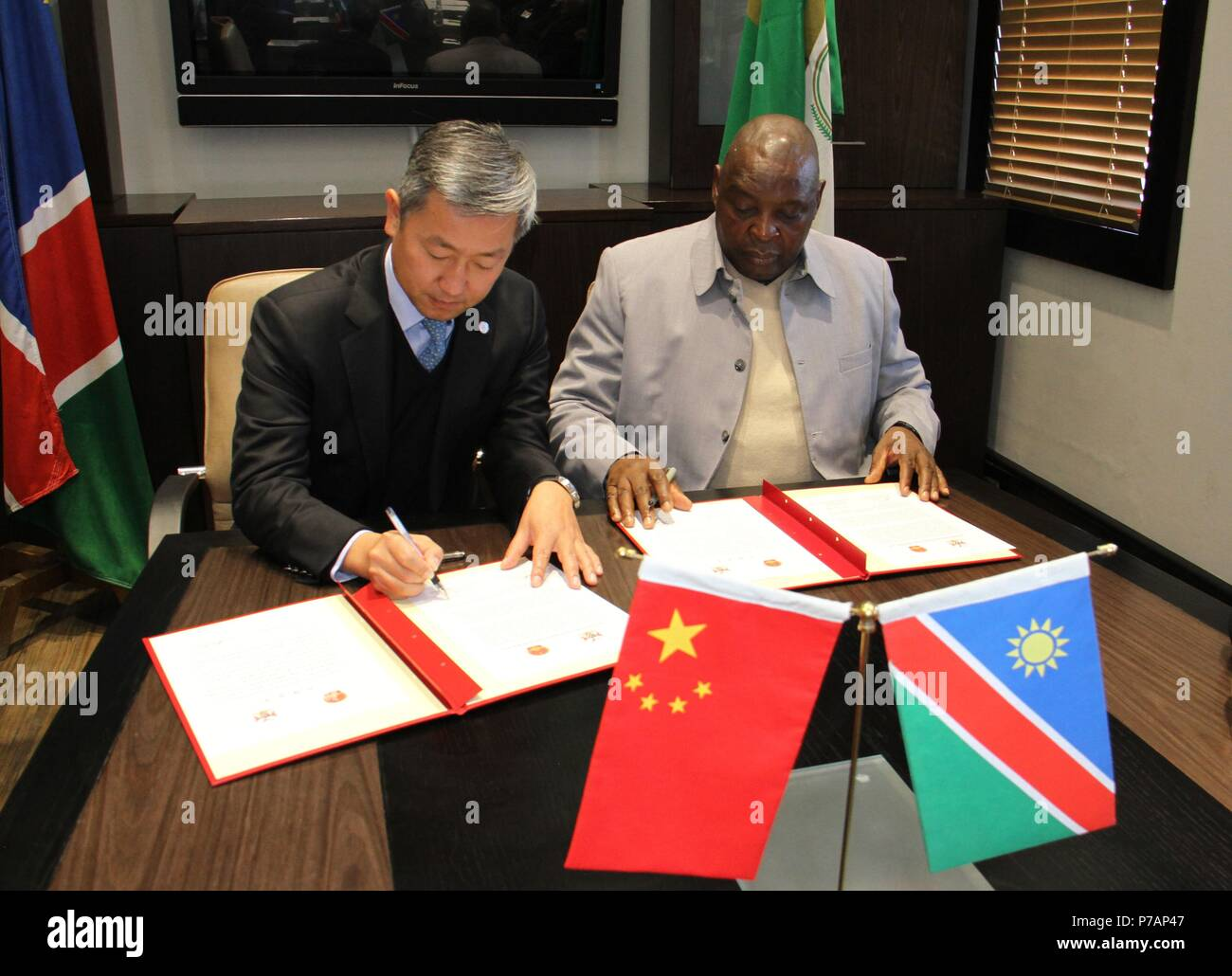 Windhoek, Namibia. 5th July, 2018. Chinese Ambassador to Namibia Zhang Yiming (L) and Namibia's Deputy Minister of Works and Transport James Sankwasa sign documents at a handover ceremony of meteorological equipment in Windhoek, capital of Namibia, on July 5, 2018. Meteorological equipment worth 2.4 million U.S. dollars donated by China were handed over to Namibia on Thursday. Credit: Wu Changwei/Xinhua/Alamy Live News - Stock Image