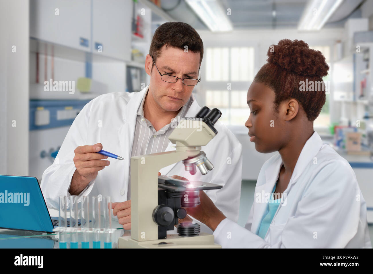Scientists, senior Caucasian male and young African female, work with a microscope in research laboratory. Shallow DOF, focus on the face of the man. - Stock Image