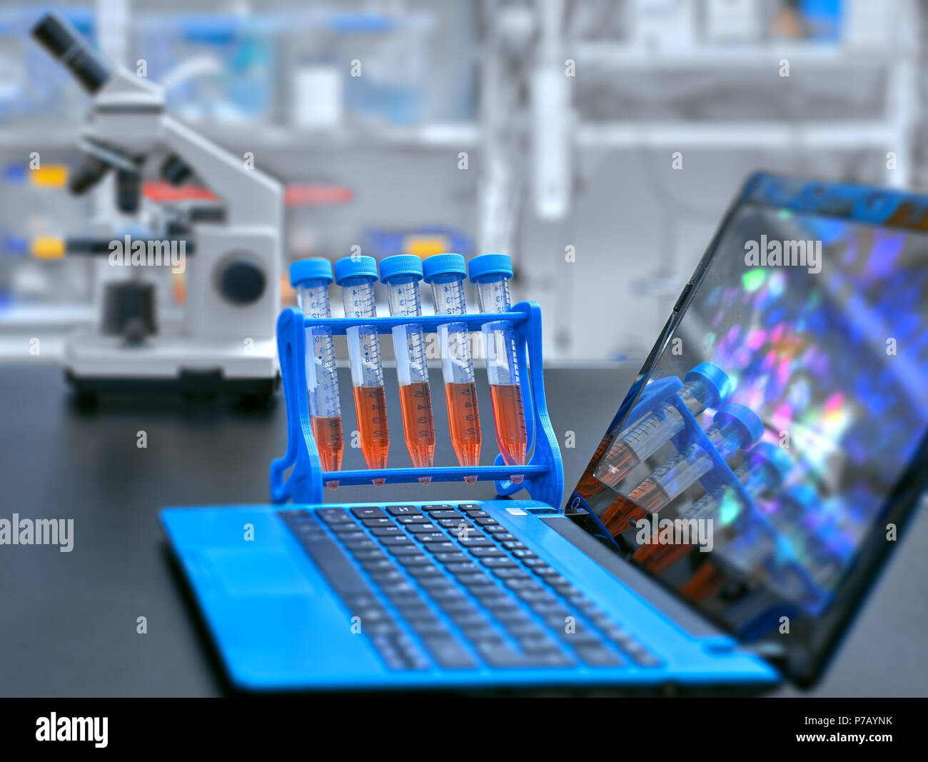 Microscope, liquid samples and portable computer with microscopic image on observation table, set up in modern laboratory - Stock Image