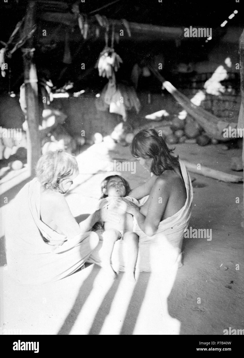 125 Gammal medicinkvinna botar ett barn som dess moder håller i knät - SMVK - 004914 - Stock Image