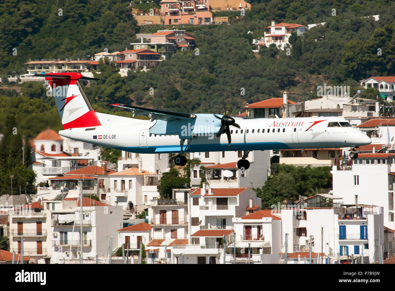 Austrian Airlines Bombardier Dash 8-400 on final at Skiathos airport carrying austrian holidaymakers from Graz with Skiathos Town in the background - Stock Image