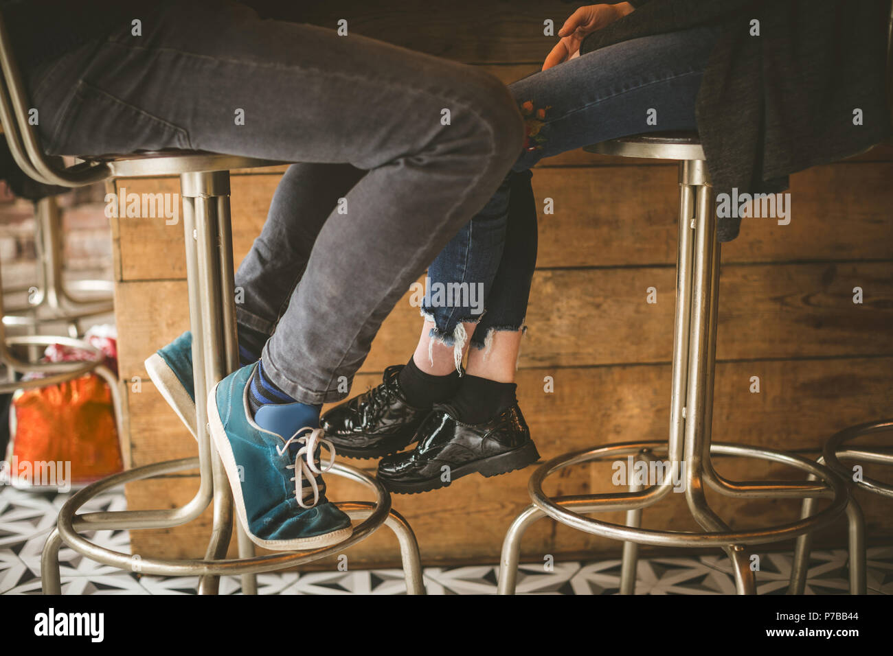 Legs of couple sitting at bar counter - Stock Image