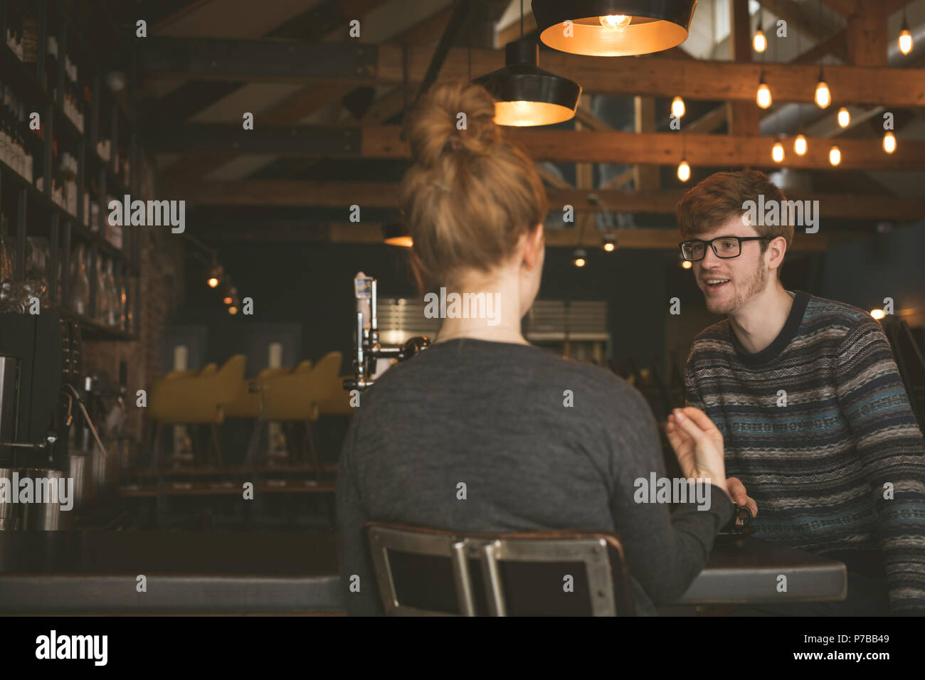 Couple talking to each other at bar counter - Stock Image