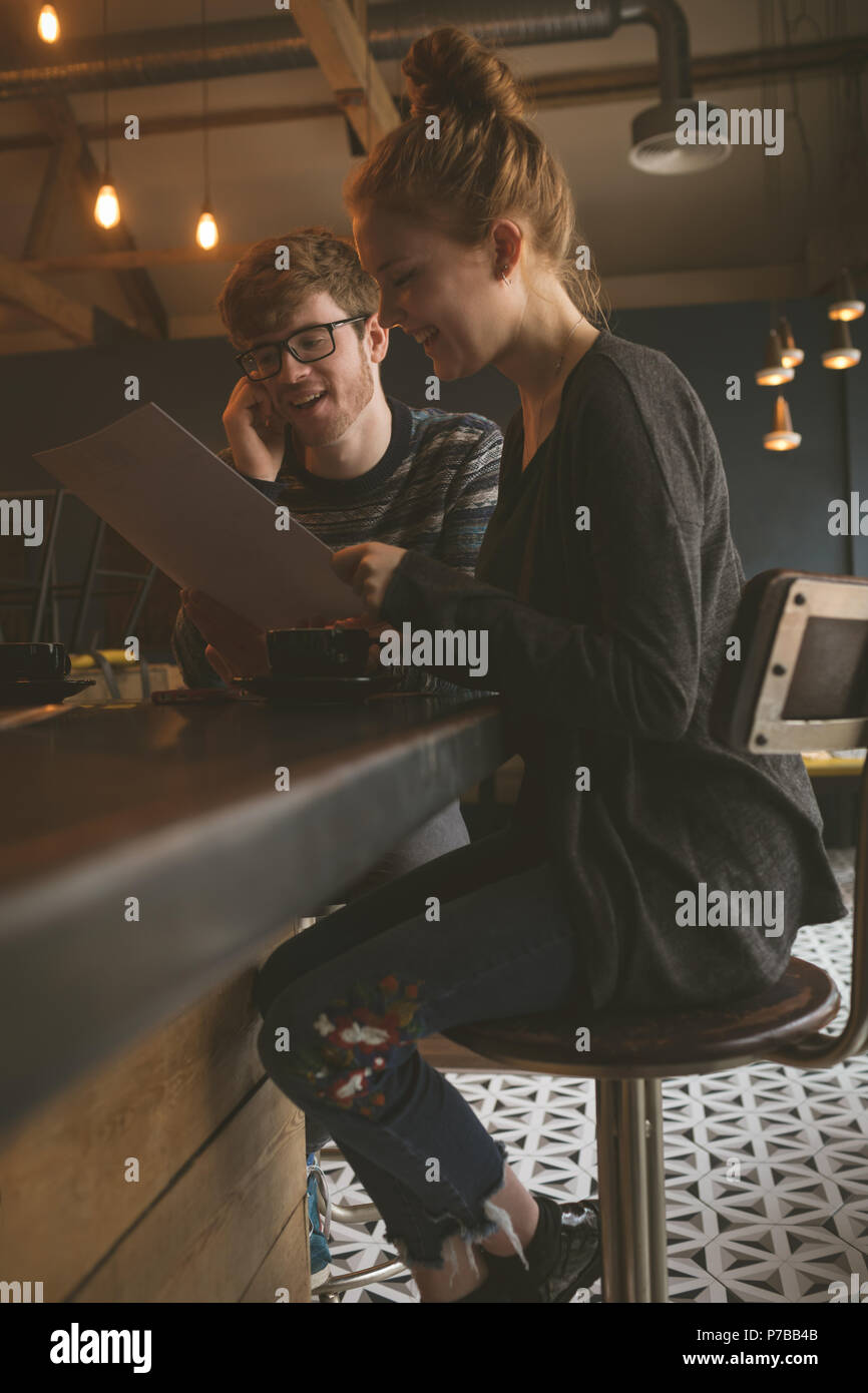 Couple checking the menu card at restaurant - Stock Image