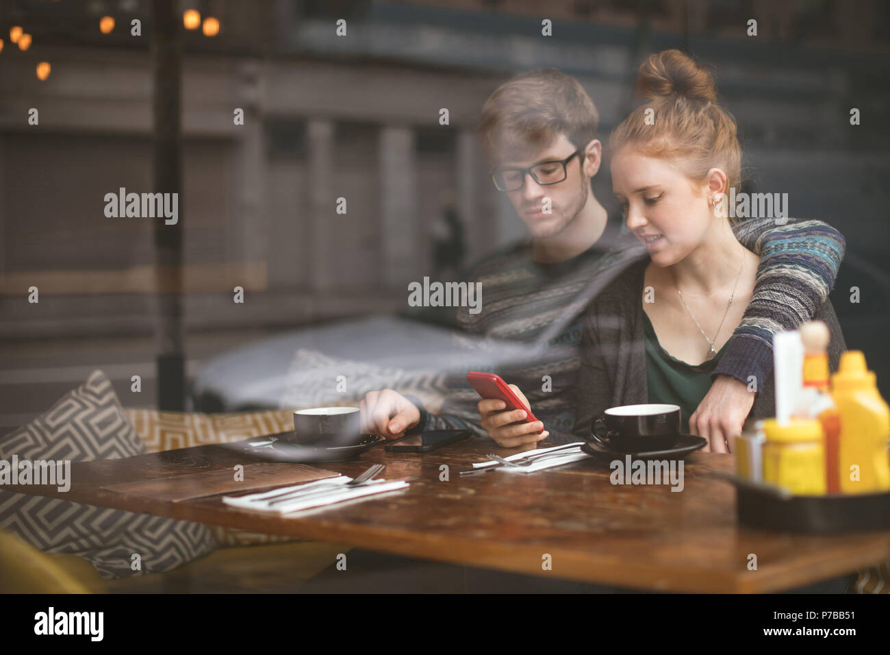 Couple using mobile phones in the cafe - Stock Image