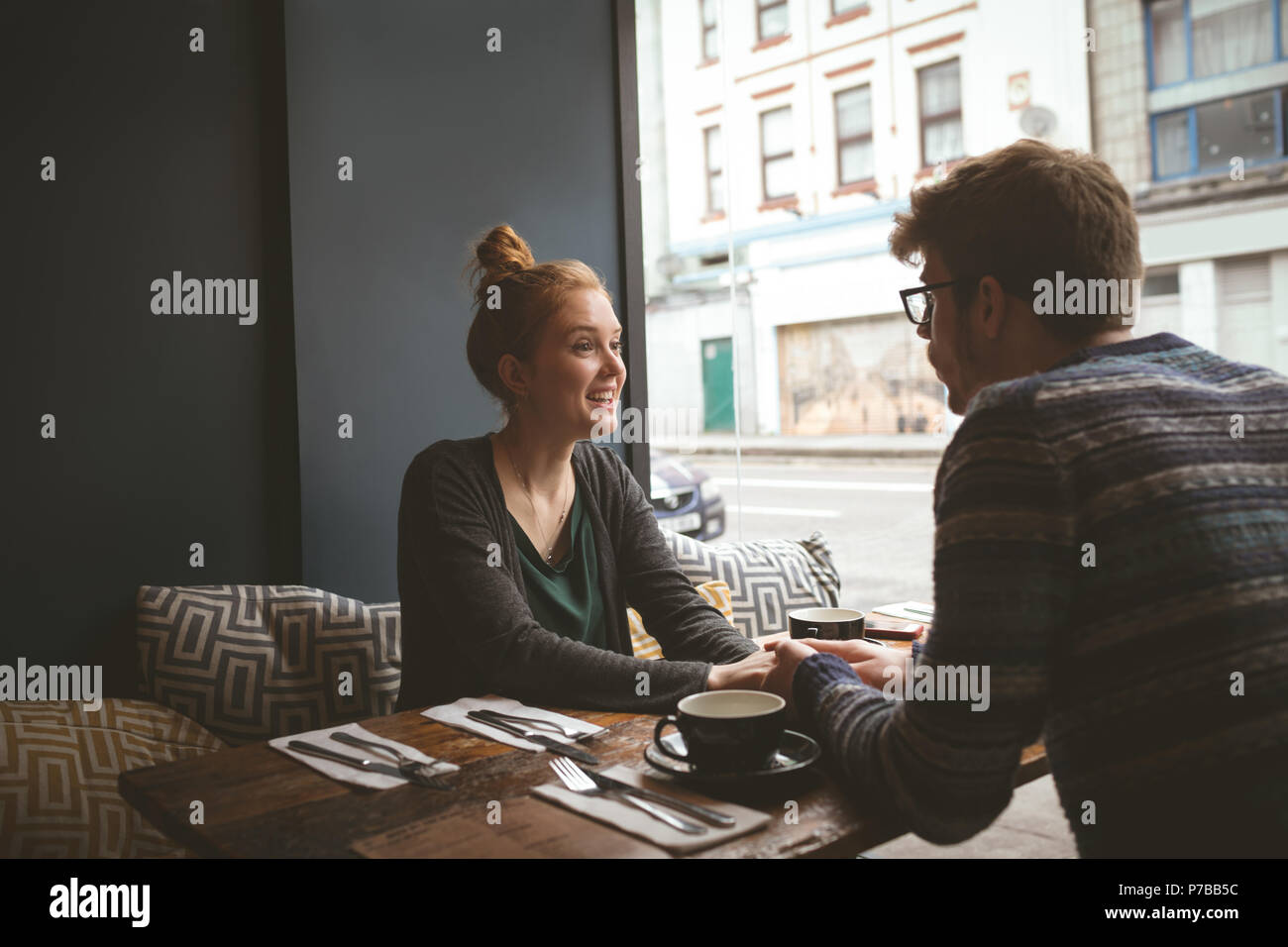 Couple holding hands in the cafe - Stock Image