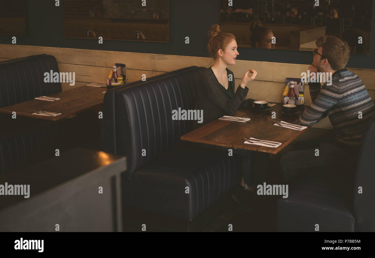 Couple talking to each other at the restaurant - Stock Image