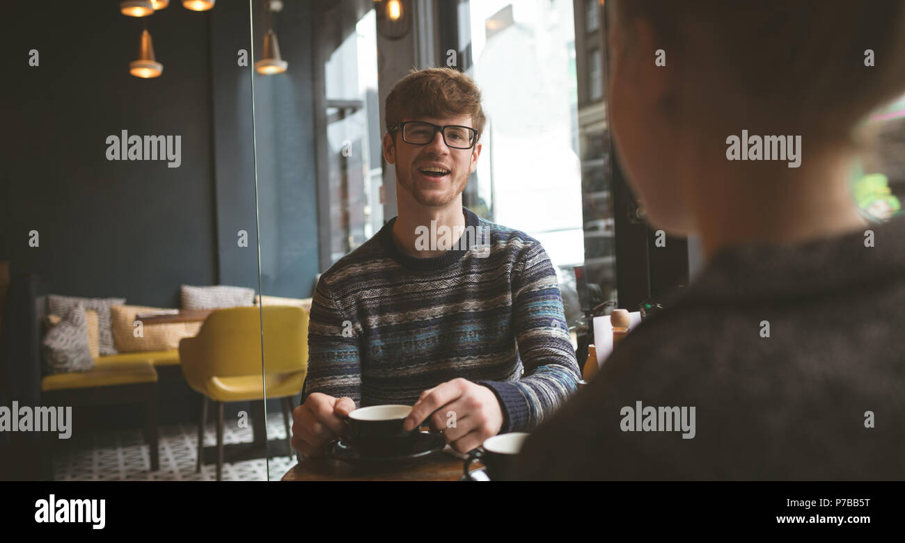 Smiling man talking to woman in cafe Stock Photo