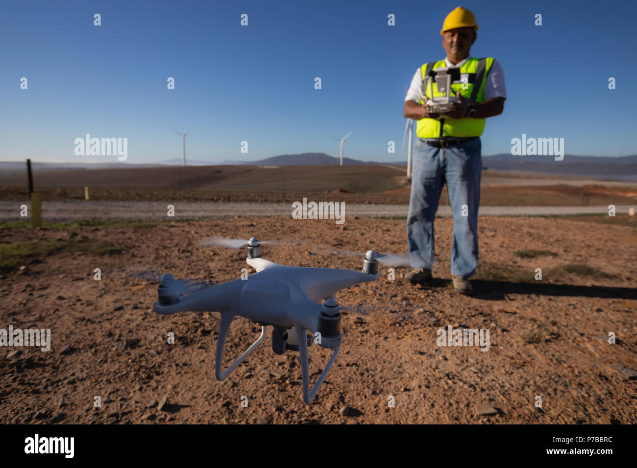 Engineer controlling a drone with a controller - Stock Image